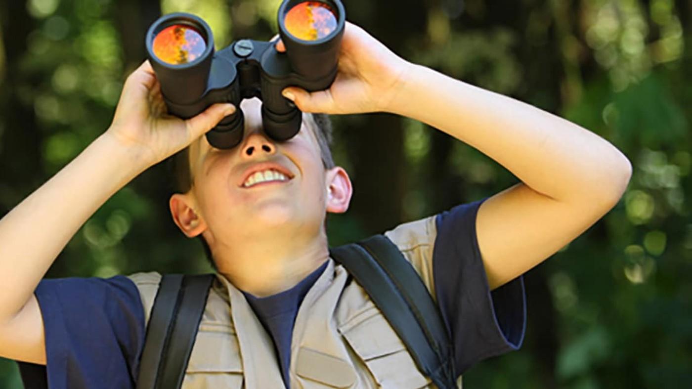 Niño explotando la naturaleza con los binoculares