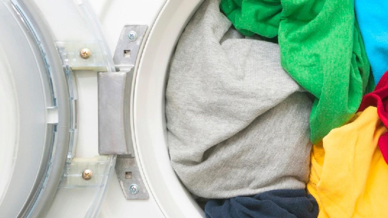 Varias prendas de tonos verdes y amarillos reposan dentro de un canasto blanco de plástico