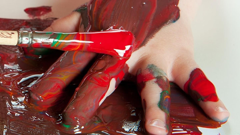 Manos pequeñas de niño manchadas de pintura