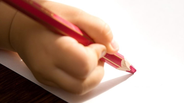 Niño escribiendo en un papel