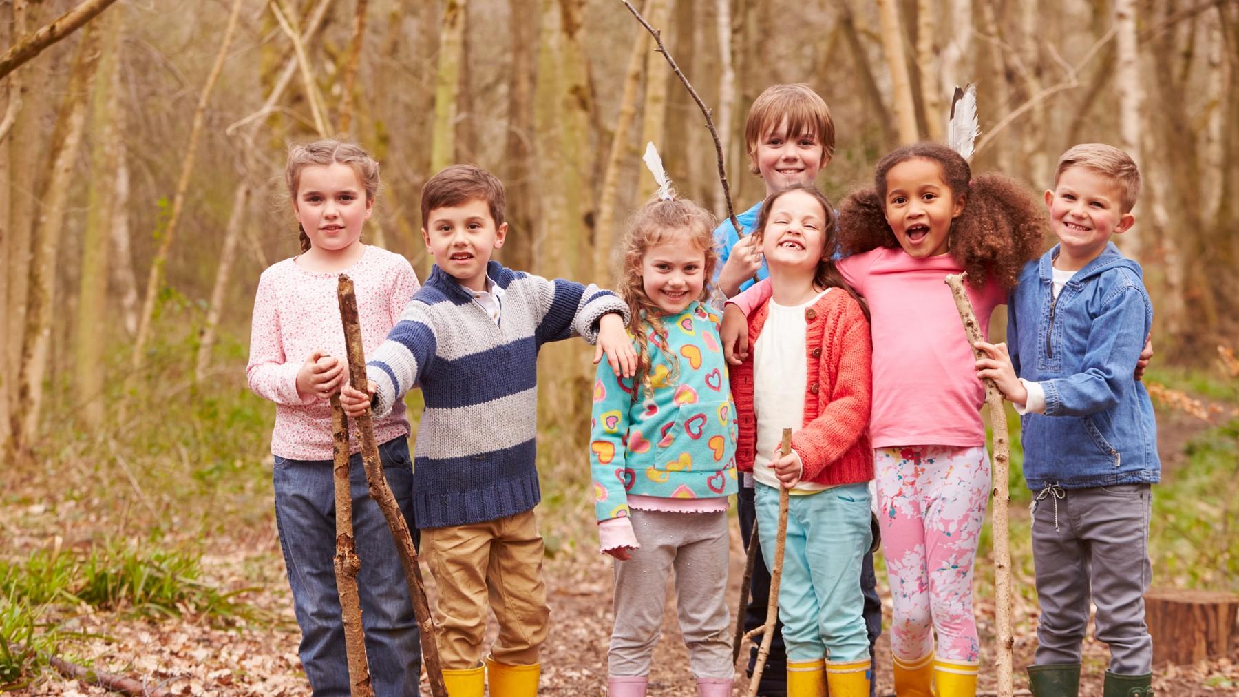 Niños jugando con ramas en el campo