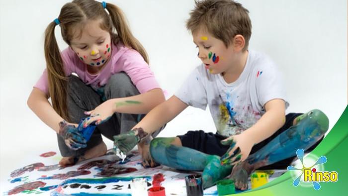 Con pinturas de colores dos niños juegan