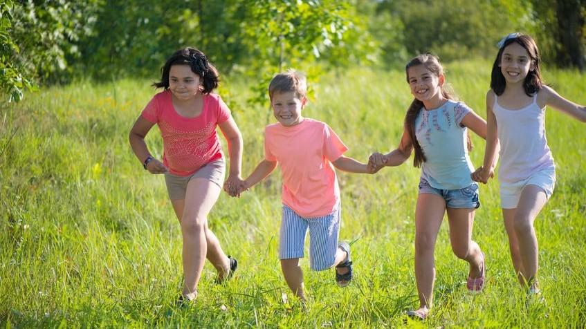 Niños agarrados de las manos corriendo