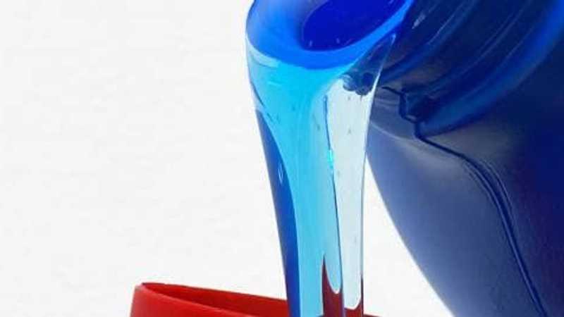 Detergente líquido que fluye del vaso a una tapa