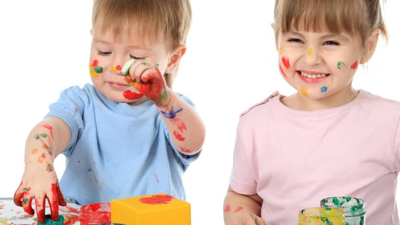 Un par de niños pequeños juega con pinturas de colores