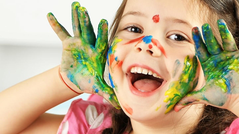Niña jugando con acuarelas de colores