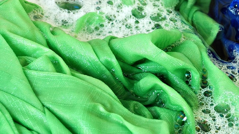 Prendas de diferentes colores sumergidas en agua y jabón