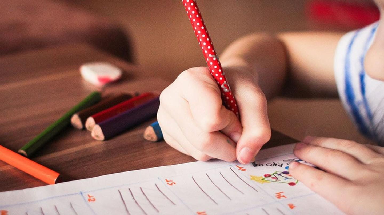 Un niño dibuja con lápices de colores sobre una hoja de papel