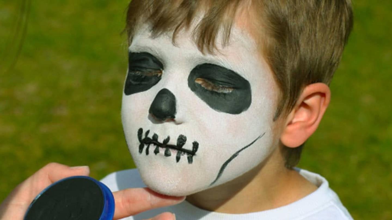 Niño con su cara pintada como una máscara de calavera