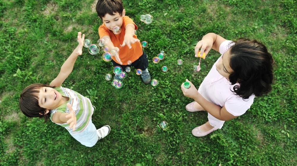 Chicos jugando con burbujas de jabon
