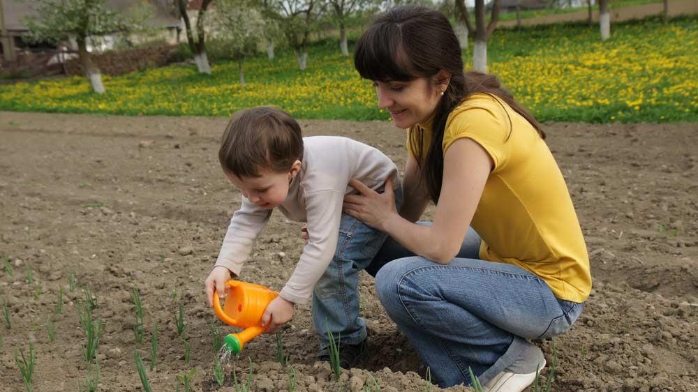 Madre e hijos regando las plantas