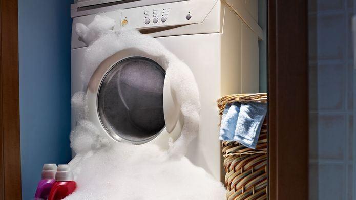Una gran cantidad de espuma de jabón reboza la capacidad de una lavadora