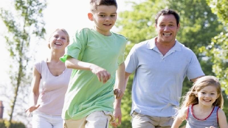 Una familia juega y corre detrás de un balón en un prado